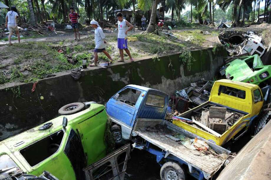 Residents walk past mangled vehicles along a canal in Cagayan de Oro on the island of Mindanao in the southern Philippines a day after Tropical Storm Washi wrought havoc in the city. Rescuers are working amid the stench of death. Photo: TED ALJIBE, AFP/Getty Images / 2011 AFP