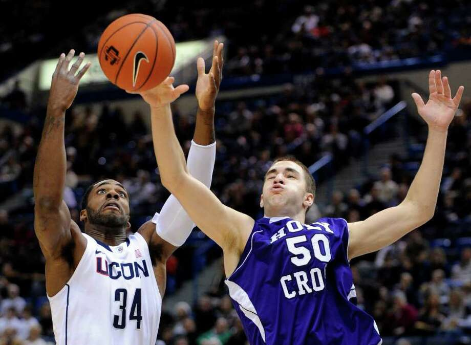 Connecticut's Alex Oriakhi (34) fights for a rebound with Holy Cross' Dave Dudzinski (50) during the first half of an NCAA college basketball game in Hartford, Conn., on Sunday, Dec. 18, 2011. (AP Photo/Fred Beckham) Photo: Fred Beckham, Associated Press / FR153656 AP