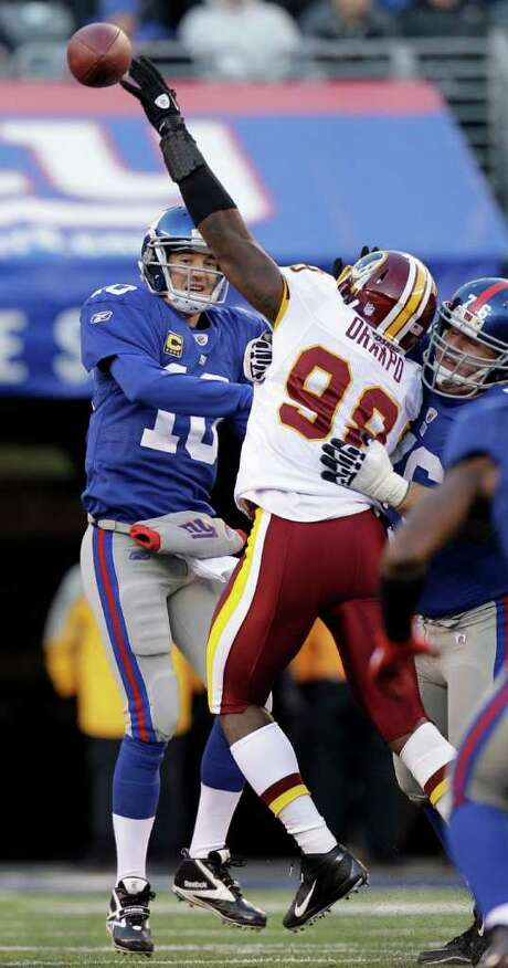 The Redskins' Brian Orakpo bats down a pass from Giants quarterback Eli Manning. Photo: AP