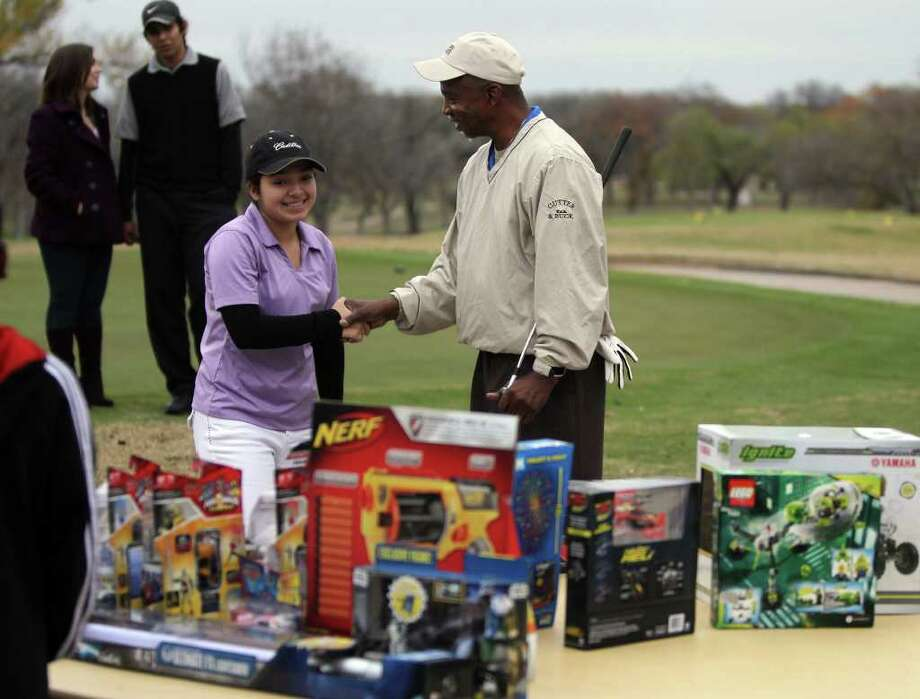 Larry Whitfield, (right) founder and president of the San Antonio Junior Golf Foundation, shakes hands with Autumn Silva,15, (center) at the Pecan Valley Golf Club Sunday December 18, 2011. Partnering with the San Antonio Minority Golf Association, both groups teach kids about golf and the importance of education. Silva was ready to take her pick from a toy drive at the weekly golf practice.  JOHN DAVENPORT/jdavenport@express-news.net Photo: SAN ANTONIO EXPRESS-NEWS