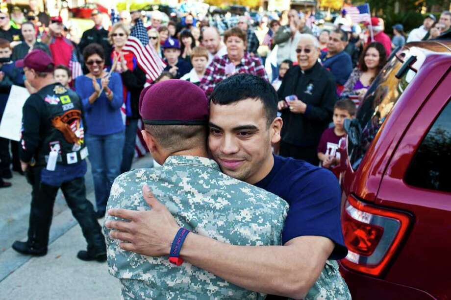 Spc. Ryan Calderon, left, and Cpl. Matt Morales hug during a send-off for Calderon and a welcome home for Morales. Calderon leaves for his first tour in Afghanistan and is with the 82nd Airborne. Cpl Morales has served one tour of Iraq and one in Afghanistan. He has served his country for 4 years and is coming home to the Houston area for good, Dec. 18, 2011 in Humble, TX. Photo: Eric Kayne, For The Chronicle / © 2011 Eric Kayne