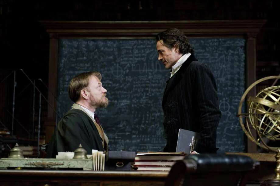 "In this image released by Warner Bros. Pictures, Jared Harris portraying Professor James Moriarty, left, and Robert Downey Jr., portraying Sherlock Holmes, are shown in a scene from ""Sherlock Holmes: A Game of Shadows."" Moriarty, who has loomed as the grandfather of all super-villains, is played with cool, quiet, chilling detachment by Jared Harris. (AP Photo/Warner Bros. Pictures, Daniel Smith) Photo: Daniel Smith"