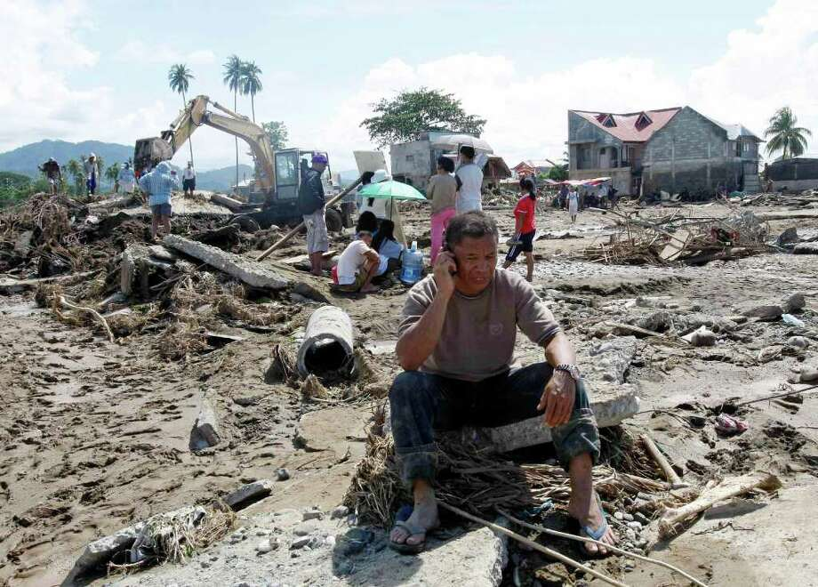 Cristio Tingson, foreground, talks on his cell phone as workers use a backhoe to search for victims of his buried house Sunday, Dec. 18, 2011 at Iligan city in southern Philippines. Tropical storm Washi blew away Sunday after devastating the southern Philippines with flash floods that killed hundreds of people as they slept and turned two coastal cities into a muddy wasteland filled with overturned cars and uprooted trees. Rescuers dug up eleven bodies but not Tingson's wife and three children. (AP Photo/Bullit Marquez) Photo: Bullit Marquez / AP