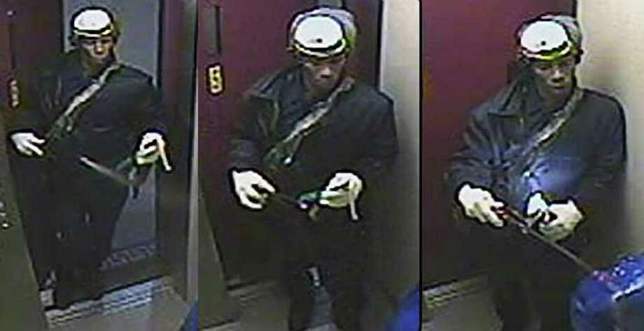 NYPD via ASSOCIATED PRESS CHILLING: Surveillance photos show a man dressed as an exterminator as he entered an elevator where he sprayed a woman with liquid before setting her afire with a Molotov cocktail. / New York Police Department