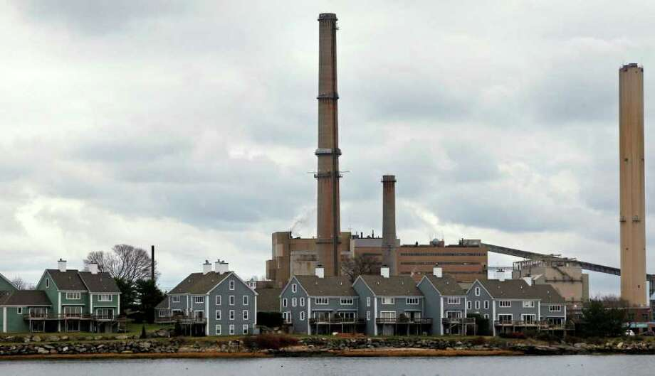 In this photo taken Wednesday, Dec. 14, 2011, the stacks of Dominion's power plant tower over a nearby neighborhood in Salem, Mass. More than 32 mostly coal-fired power plants in a dozen states will be forced to shut down and another 34 might have to close because of new federal air pollution regulations, according to an Associated Press survey.  Together, those plants produce enough electricity for more than 21 million households, but their demise is unlikely to cause homes to go dark.  (AP Photo/Charles Krupa) Photo: Charles Krupa / AP