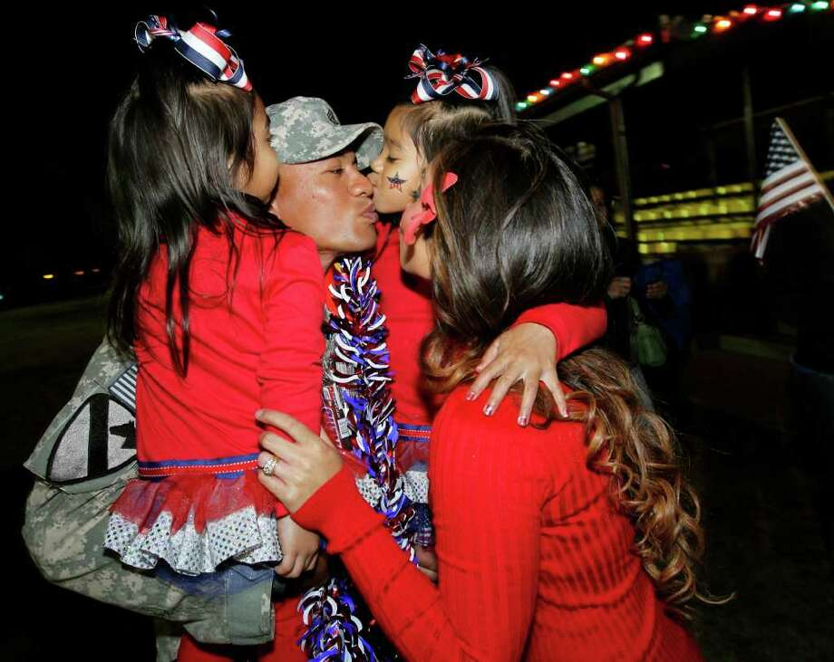 ERICH SCHLEGEL : ASSOCIATED PRESS DADDY'S HOME: U.S. Army Staff Sgt. Elama Palemene is kissed by his wife, Annaden, right, and children Ko' Elani, left, and Pe' Ela during an early morning welcome home ceremony at Fort Hood near Killeen for about 300 U.S. Army 1st Cavalry 2nd Brigade soldiers returning home as the last U.S. combat troops leave Iraq. Photo: Erich Schlegel / FR 62355 AP