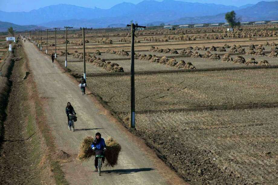 In this Tuesday, Oct. 25, 2011 photo, North Korean farmers pass along a road past farm fields at a collective farm near the town of Sariwon, North Korea. In a landmark shift after three years of tensions, the United States is poised to announce in the coming days its first significant donation of food aid to North Korea _ a small but symbolic offer that is expected to pave the way for long-stalled discussions on dismantling Pyongyang's nuclear program. (AP Photo/David Guttenfelder) Photo: David Guttenfelder