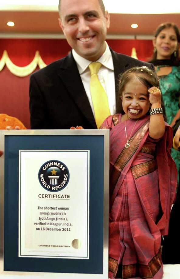 MANISH SWARUP : ASSOCIATED PRESS IT'S OFFICIAL : Eighteen-year-old Jyoti Amge smiles after getting the title of the shortest woman by the Guinness World Records adjudicator Rob Molloy, in Nagpur, India, last week. Photo: Manish Swarup / AP