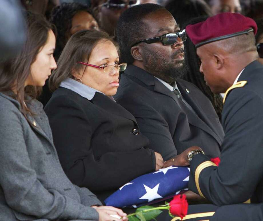 From left, Hickman's wife Cali Kim Hickman, Veronica Hickman (mother) and David Hickman (father) as Major General Rodney O. Anderson hands a folded flag that draped the coffin to Hickman's mother during the burial of Army Specialist David Hickman with full military honors at Lakeview Memorial Park, on Saturday, Nov. 26, 2011, in Greensboro, N.C. Nearly 4,500 American fighters died before the last U.S. troops crossed the border into Kuwait. David Hickman, 23, of Greensboro was the last of those war casualties, killed in November by the kind of improvised bomb that was a signature weapon of this war. (AP Photo/ News & Record, Joseph Rodriguez) Photo: Joseph Rodriguez / News & Record