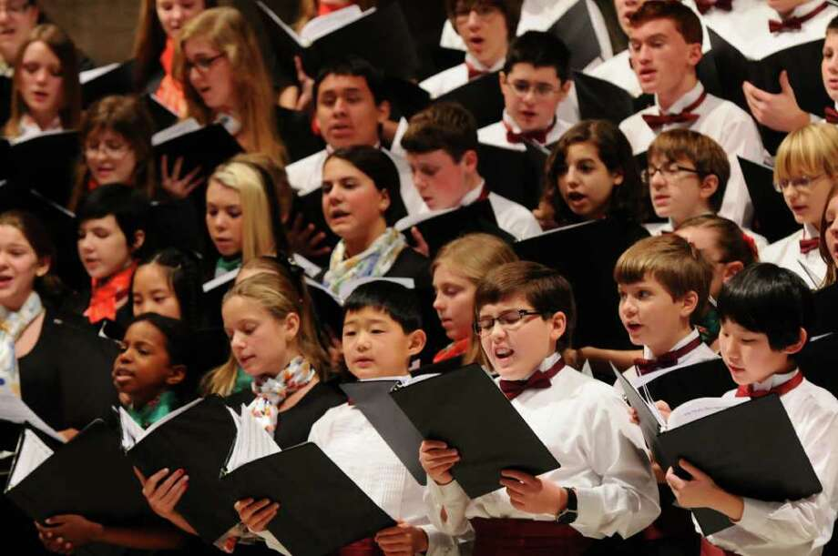 Andre Valverde of Altamont, 10, third from right wearing glasses at bottom, sings during the Capital District Youth Chorale at St. Paul's Episcopal Church on Sunday  Dec. 18, 2011, in Albany, N.Y. (Philip Kamrass / Times Union ) Photo: Philip Kamrass / 00015792A