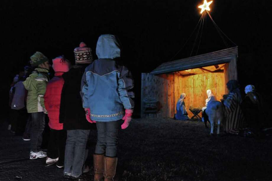 Children watch the live nativity performed by the youth group from the Bethlehem Lutheran Church on Sunday evening Dec. 18, 2011, in Delmar, N.Y. Chris Brands, 16, left, played Joseph for the fourth time, while Anna Barfield, 17, played Mary. The church youth group has performed the live nativity for over 30 years.  (Philip Kamrass / Times Union ) Photo: Philip Kamrass / 00015608B