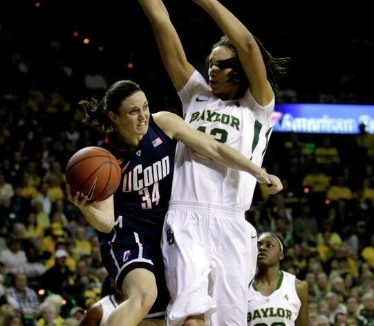 Connecticut guard Kelly Faris (34) looks to pass as Baylor center Brittney Griner defends beneath the basket in the first half of an NCAA college basketball game, Sunday, Dec. 18, 2011, in Waco, Texas. (AP Photo/Tony Gutierrez) Photo: Tony Gutierrez, Associated Press / AP