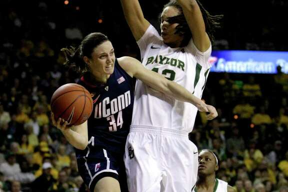 Connecticut guard Kelly Faris (34) looks to pass as Baylor center Brittney Griner defends beneath the basket in the first half of an NCAA college basketball game, Sunday, Dec. 18, 2011, in Waco, Texas. (AP Photo/Tony Gutierrez)