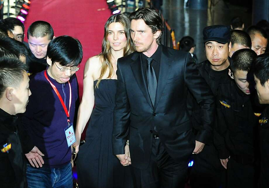 "Oscar winning actor Christian Bale arrives on the red carpet with his wife Sibi for the screening of the film ""The Flowers of War,"" in Beijing on December 12, 2011.  Oscar winning actor Christian Bale defended the upcoming Nanjing Massacre film ""The Flowers of War,"" by China's most famous director, Zhang Yimou, as more than an anti-Japanese propaganda film. In the film, Bale plays an American drifter who becomes the unwitting protector of a group of Chinese schoolgirls and prostitutes trying to escape the Japanese army's brutal sacking of China's wartime capital.          AFP PHOTO/Mark RALSTON (Photo credit should read MARK RALSTON/AFP/Getty Images) Photo: Mark Ralston, AFP/Getty Images"