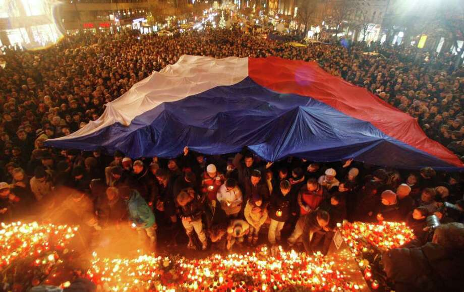 People gather under a Czech national flag as thousands mark the passing of former Czech president Vaclav Havel at the Venceslaw's square in Prague, Czech Republic, Sunday, Dec. 18, 2011. Havel, the dissident playwright who wove theater into politics to peacefully bring down communism in Czechoslovakia and become a hero of the epic struggle that ended the Cold War, died Sunday Dec. 18, 2011 in Prague. He was 75. (AP Photo/Petr David Josek) Photo: Petr David Josek / AP
