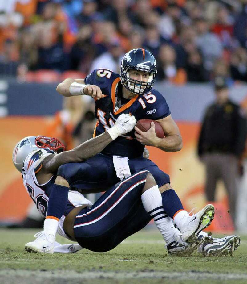 MARC PISCOTTY: GETTY IMAGES DOWN GOES TEBOW: Denver's Tim Tebow is wrapped up by New England's Mark Anderson for a sack in the fourth quarter. Photo: Marc Piscotty / 2011 Getty Images