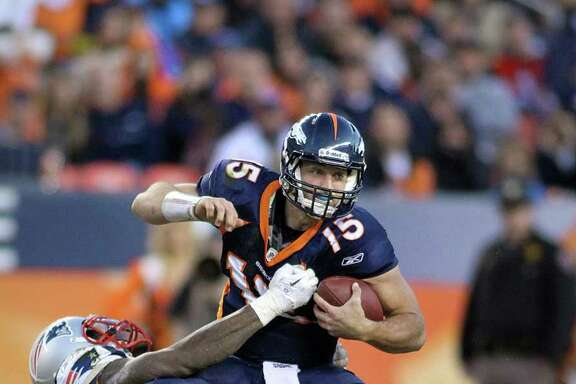 MARC PISCOTTY: GETTY IMAGES DOWN GOES TEBOW: Denver's Tim Tebow is wrapped up by New England's Mark Anderson for a sack in the fourth quarter.