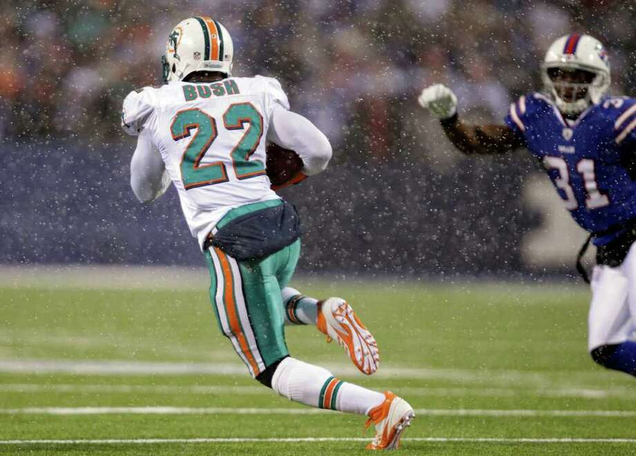 Miami Dolphins' Reggie Bush (22) runs for a long touchdown under pressure from Buffalo Bills' Jairus Byrd (31)  during the second half of an NFL football game in Orchard Park, N.Y., Sunday, Dec. 18, 2011. The Dolphins won 30-23. (AP Photo/David Duprey) Photo: David Duprey