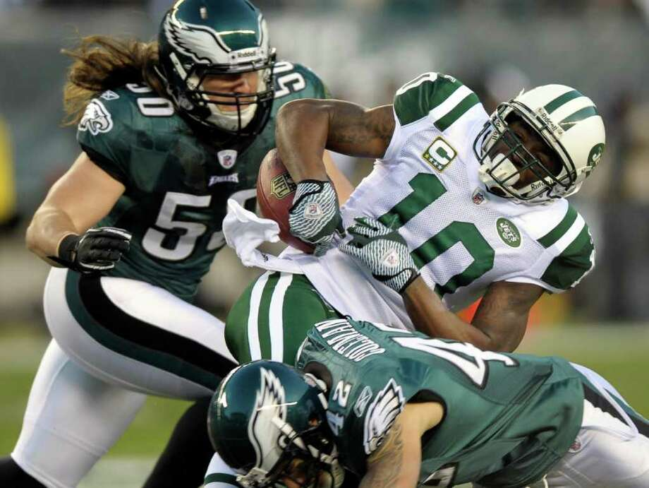 New York Jets wide receiver Santonio Holmes (10) loses control of the ball as he is hit by Philadelphia Eagles middle linebacker Casey Matthews (50) and strong safety Kurt Coleman (42) in the first half of an NFL football game Sunday, Dec. 18, 2011 in Philadelphia. Philadelphia Eagles defensive end Juqua Parker picked up the fumble and ran for a touchdown. (AP Photo/Michael Perez) Photo: Michael Perez