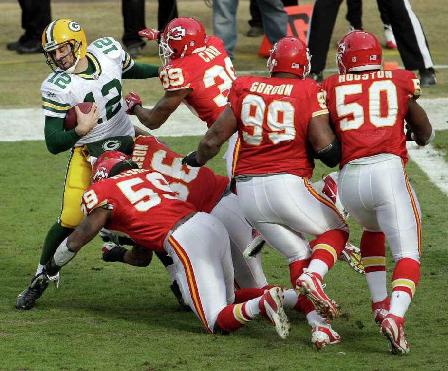 Green Bay Packers quarterback Aaron Rodgers (12) is tackled by a group of Kansas City Chiefs defenders during the second half of an NFL football game Sunday, Dec. 18, 2011, in Kansas City, Mo. The Chiefs won 19-14, handing the Packers their first loss of the season. (AP Photo/Charlie Riedel) Photo: Charlie Riedel