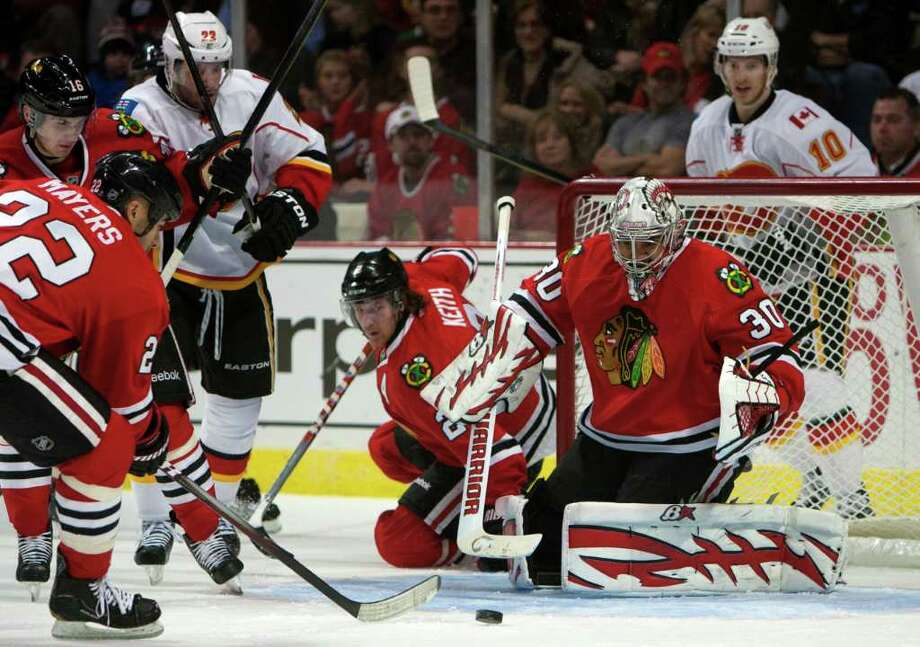 Chicago Blackhawks' Jamal Mayers (22) clears the puck after a save by goalie Ray Emery (30) against the Calagary Flames during the first period of an NHL game in Chicago on Sunday, Dec. 18, 2011.  (AP Photo/Charles Cherney) Photo: Charles Cherney