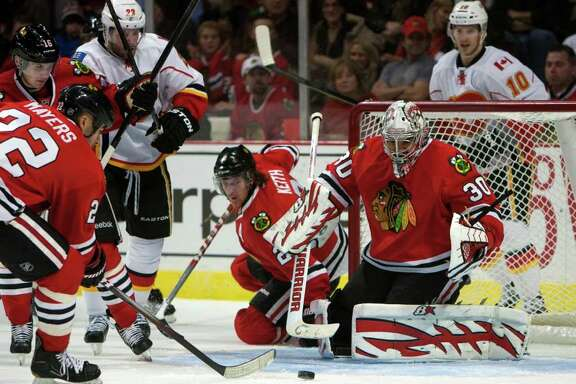Chicago Blackhawks' Jamal Mayers (22) clears the puck after a save by goalie Ray Emery (30) against the Calagary Flames during the first period of an NHL game in Chicago on Sunday, Dec. 18, 2011.  (AP Photo/Charles Cherney)