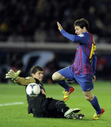 YOSHIKAZU TSUNO: AFP/GETTY IMAGES SERIOUS TROUBLE: Barcelona's Lionel Messi has Santos goalie Rafael Cabral in a precarious position before scoring his second goal Sunday in Club World Cup final. Photo: YOSHIKAZU TSUNO / AFP
