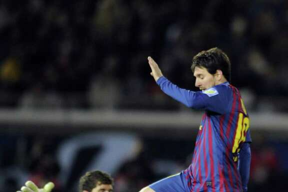YOSHIKAZU TSUNO: AFP/GETTY IMAGES SERIOUS TROUBLE: Barcelona's Lionel Messi has Santos goalie Rafael Cabral in a precarious position before scoring his second goal Sunday in Club World Cup final.
