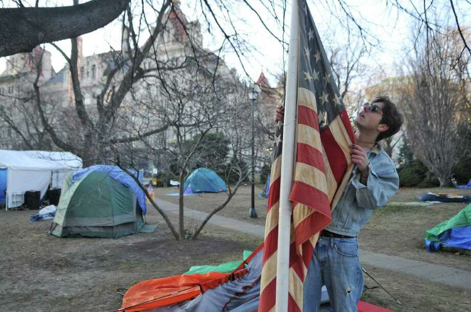Nicholas Reed of Niskayuna looks over an American flag while visiting Academy Park at the Occupy Albany site on Sunday Dec. 18, 2011, in Albany, N.Y.  Reed said that he went to the area to take photographs for his portfolio for an art school application, and wandered onto the encampment. (Philip Kamrass / Times Union ) Photo: Philip Kamrass / 00015819A
