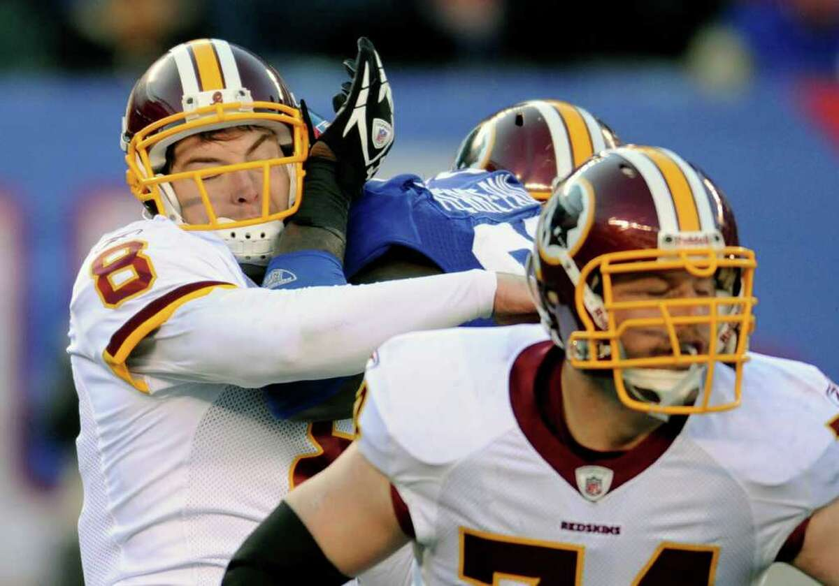 Washington Redskins' Rex Grossman, left, is hit by New York Giants' Jason Pierre-Paul, center, during the second quarter of an NFL football game on Sunday, Dec. 18, 2011, in East Rutherford, N.J. Pierre-Paul was penalized for roughing the passer. The Redskins defeated the Giants 23-10. (AP Photo/Bill Kostroun)