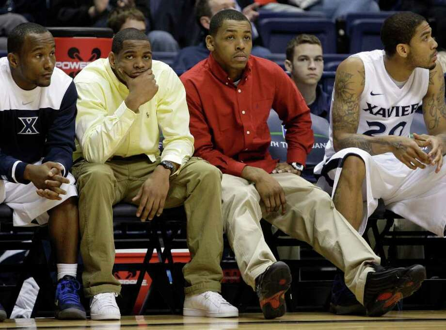 Xavier guards Tu Holloway, center left, and Mark Lyons, center right, sit on the bench with O'Neil Cooper, left, and Justin Martin (20) in the second half of an NCAA college basketball game against Oral Roberts, Sunday, Dec. 18, 2011, in Cincinnati. Holloway and Lyons were serving suspensions for their part in a fight against Cincinnati last week. Oral Roberts won 64-42. (AP Photo/Al Behrman) Photo: Al Behrman