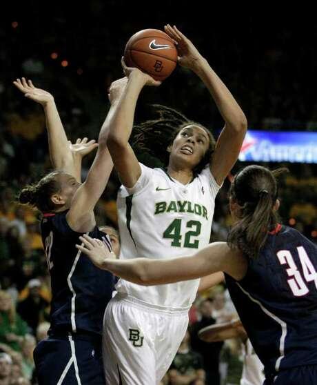 TONY GUTIERREZ: ASSOCIATED PRESS GRINDING AWAY: Baylor's Brittney Griner draws the attention of Heather Buck, left, and Kelly Faris. Griner shook off the harassment by the Huskies to score 25 points. Photo: Tony Gutierrez / AP