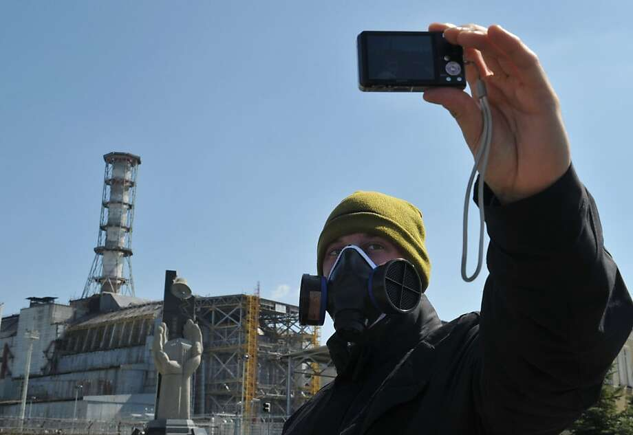 A visitor takes a selfportrait in front of the 4th power block of the Chernobyl Nuclear Power Plant on April 18, 2011. In the heart of Chernobyl, Ukrainian specialists regularly venture inside the concrete cover sheltering the ruined reactor after it exploded on April 26, 1986 to check its structure and radiation levels. AFP PHOTO / SERGEI SUPINSKY (Photo credit should read SERGEI SUPINSKY/AFP/Getty Images)  A visitor takes a selfportrait in front of the 4th power block of the Chernobyl Nuclear Power Plant on April 18, 2011. In the heart of Chernobyl, Ukrainian specialists regularly venture inside the concrete cover sheltering the ruined reactor after it exploded on April 26, 1986 to check its structure and radiation levels.   AFP PHOTO / SERGEI SUPINSKY (Photo credit should read SERGEI SUPINSKY/AFP/Getty Images) Photo: Sergei Supinsky, AFP/Getty Images