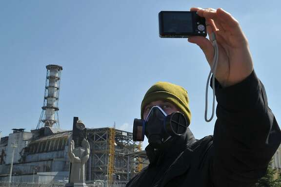 A visitor takes a selfportrait in front of the 4th power block of the Chernobyl Nuclear Power Plant on April 18, 2011. In the heart of Chernobyl, Ukrainian specialists regularly venture inside the concrete cover sheltering the ruined reactor after it exploded on April 26, 1986 to check its structure and radiation levels. AFP PHOTO / SERGEI SUPINSKY (Photo credit should read SERGEI SUPINSKY/AFP/Getty Images)  A visitor takes a selfportrait in front of the 4th power block of the Chernobyl Nuclear Power Plant on April 18, 2011. In the heart of Chernobyl, Ukrainian specialists regularly venture inside the concrete cover sheltering the ruined reactor after it exploded on April 26, 1986 to check its structure and radiation levels.   AFP PHOTO / SERGEI SUPINSKY (Photo credit should read SERGEI SUPINSKY/AFP/Getty Images)
