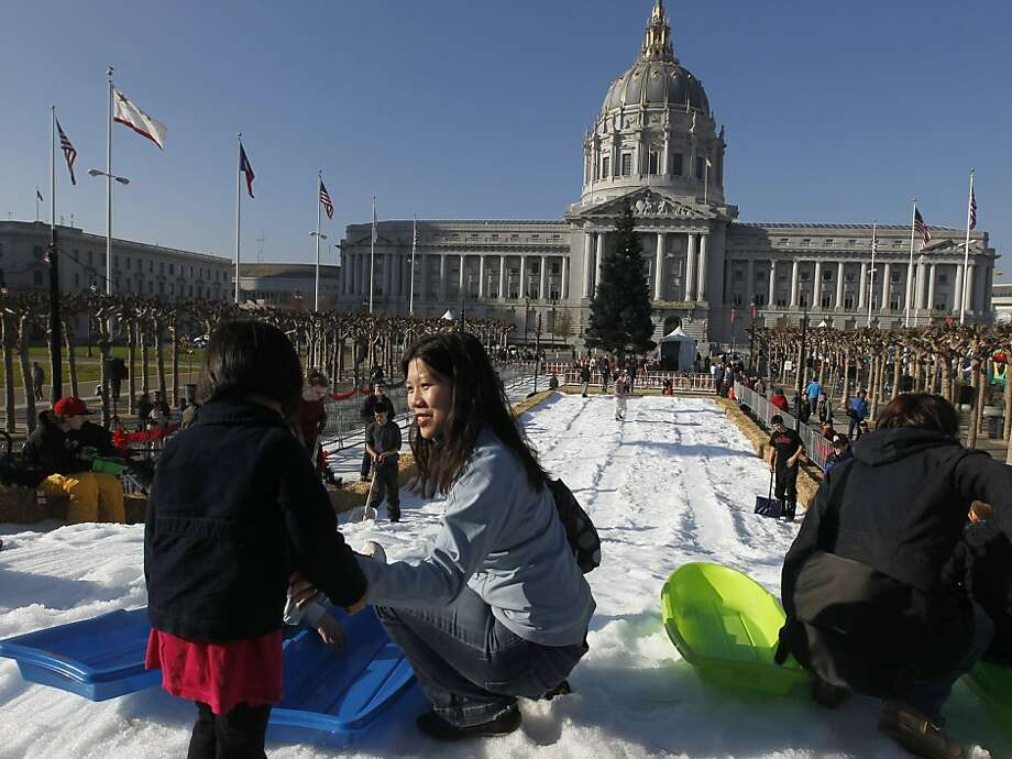 Cindy Tran helps her daughter Zoe into a sled for a ride down a snow slope across from City Hall at Civic Center Plaza in San Francisco, Calif. on Saturday, Dec. 17, 2011. Photo: Paul Chinn, The Chronicle