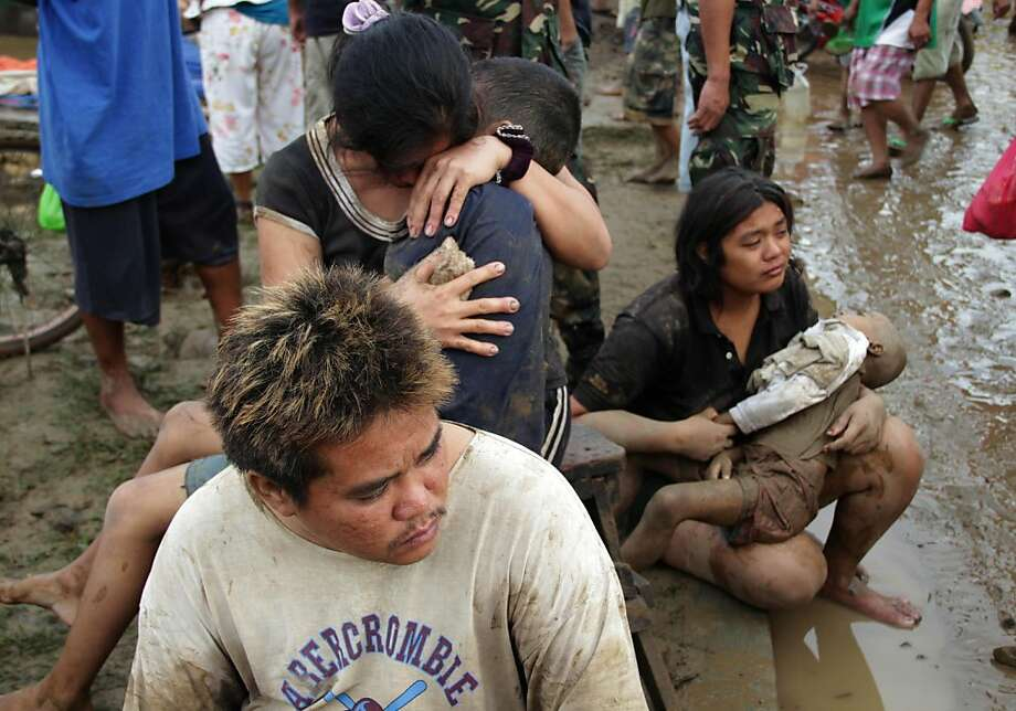 Two women hold their children killed during the passage of tropical storm Washi at a village in Iligan City, on the southern island of Mindanao on December 17, 2011.  The death toll from the tropical storm rose to 143 on december 17 with more than 100 others missing after widespread flash floods in the southern Philippines.   AFP PHOTO/Cherryl Vergeire (Photo credit should read CHERRYL VERGEIRE/AFP/Getty Images) Photo: Cherryl Vergeire, AFP/Getty Images