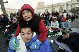 """(With hood) Tony An (cq) and (below) Yusuke Hashizume (cq) join an outdoor audience, at San Francisco's Civic Center Plaza, to enjoy a simulcast broadcast of San Francisco Opera's new production of Madama (cq) Butterfly. In this  first new experiment to shake up and generate new audiences, the San Francisco Opera - under new general manager David Gockley- simulcasts the world premiere of this production of """"Madama(cq) Butterfly""""  on a single, 16-foot x 24-foot LED screen.  (CHRISTINA KOCI HERNANDEZ/THE CHRONICLE)  **(cq)(hood)Tony An, and below is (cq)Yusuke Hashizume Ran on: 05-29-2006 Yusuke Hashizume helps hooded Tony An to a better view as they join the crowd outside City Hall taking in the San Francisco Opera's new &quo;Madama Butterfly&quo; production."""