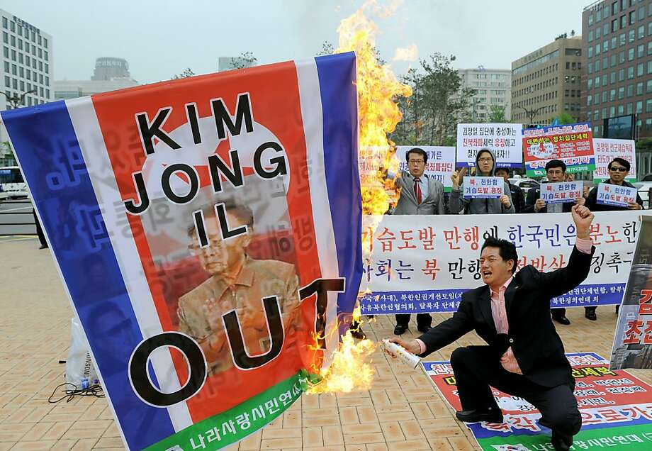 A South Korean conservative activist burns a North Korean flag showing a picture of its leader Kim Jong-Il during an anti-North Korea rally in Seoul on May 25, 2010 after South Korea announced reprisals against North Korea for the sinking of a warship. North Korean leader Kim Jong-Il ordered troops and civil organisations on combat alert after South Korea accused his country of sinking a warship, a defector group said. TOPSHOTS    AFP PHOTO/JUNG YEON-JE (Photo credit should read JUNG YEON-JE/AFP/Getty Images)(Photo Credit should Read /AFP/Getty Images)  Ran on: 05-26-2010 A South Korean conservative activist burns a North Korean flag during an anti-North Korea rally in Seoul. Photo: Jung Yeon-je, AFP/Getty Images