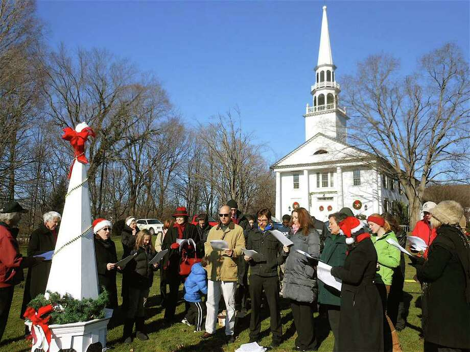 Members of Saugatuck Congregational Church sing carols on the Great Lawn of the fire-damaged church Sunday afternoon. Photo: Mike Lauterborn / Westport News contributed