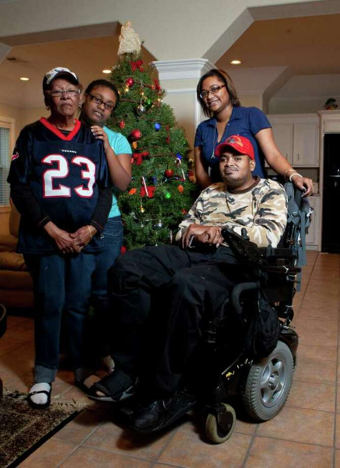 Leland Spencer, sitting, shows his Christmas tree with his mother Shirley German, left, niece Miracle Lavergne, center, and niece Krysten German, Friday, Dec. 16, 2011, in his Houston home. Photo: Nick De La Torre, Houston Chronicle / © 2011  Houston Chronicle