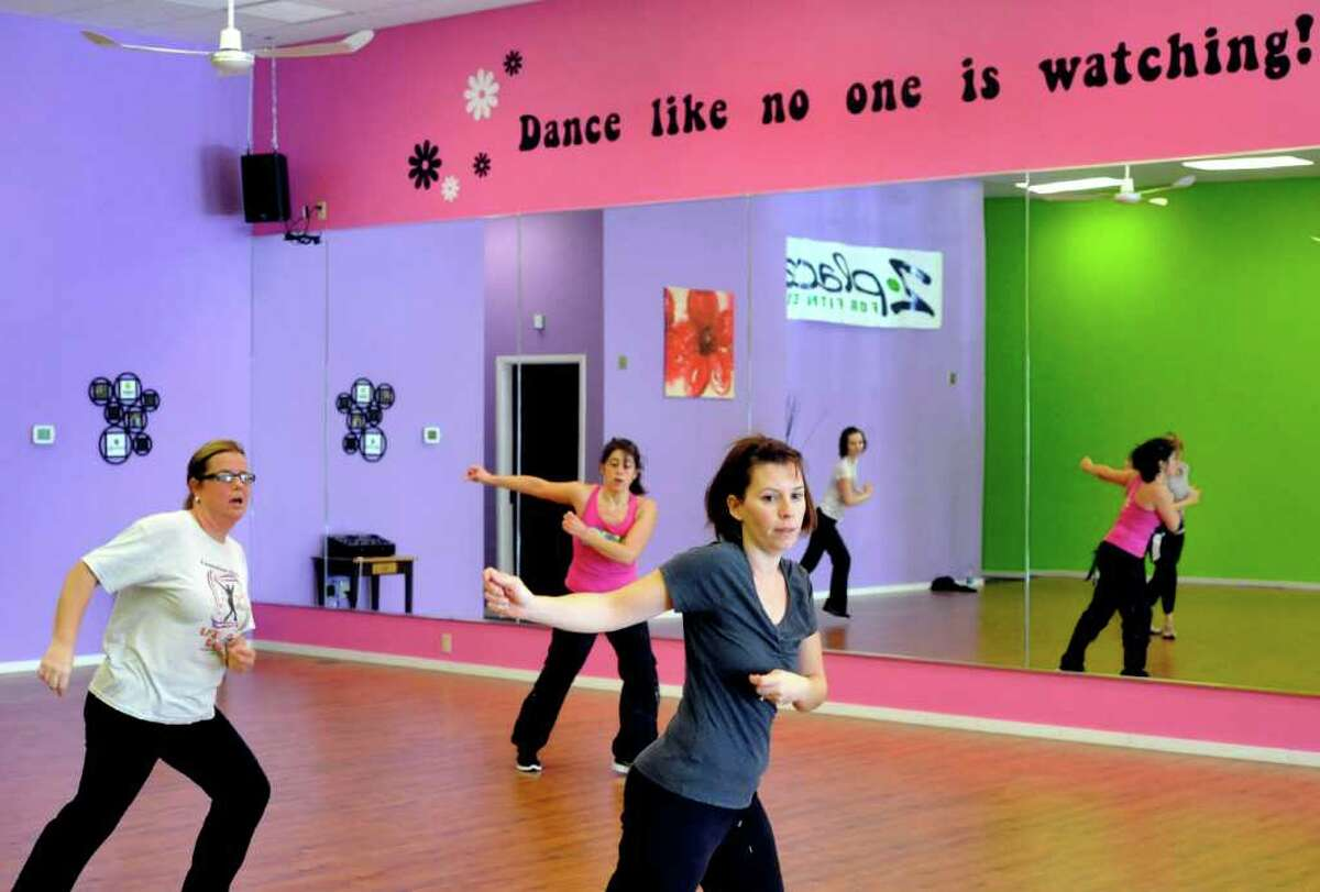 Sue Mouchantat, left, Robin Bova, instructor, and Juli Pankow, right, exercise in Zumba class at Z Place for Fitness in Newtown, Monday, Dec. 19, 2011. The studio is celebrating its one year anniversary.