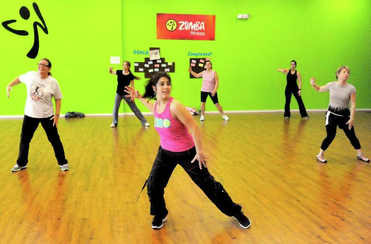 Sue Mouchantat, left, follows instructor Robin Bova in a Zumba class at Z Place for Fitness in Newtown, Monday, Dec. 19, 2011. The studio is celebrating its one year anniversary.