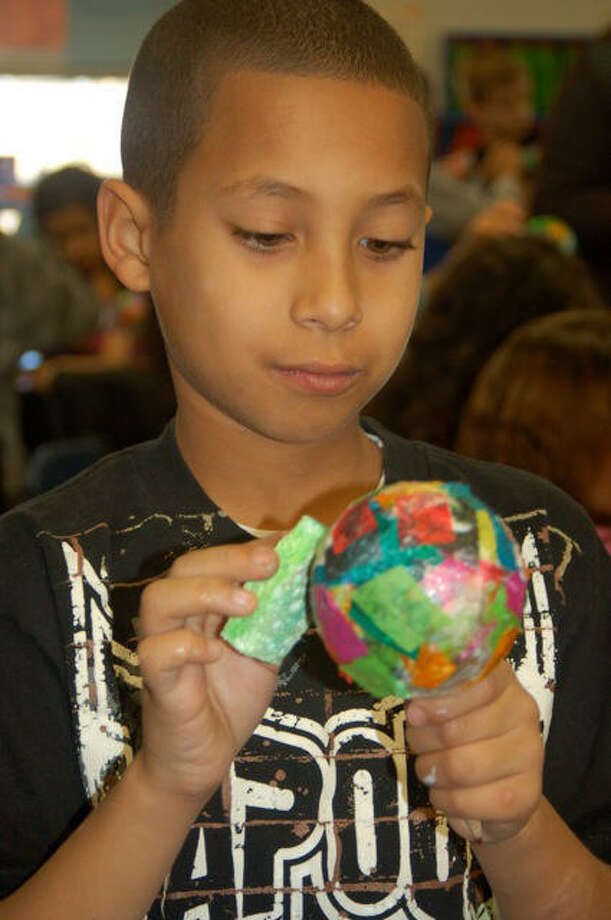 """Harmony Hills Elementary School student Sebastian Casias crafts a Christmas ornament as part of an """"Ornaments for the Planet"""" fundraiser. Ornaments made by Casias and his classmates are on sale at Whole Foods Market. Proceeds will benefit the Whole Planet Foundation. Photo: Courtesy Photo"""