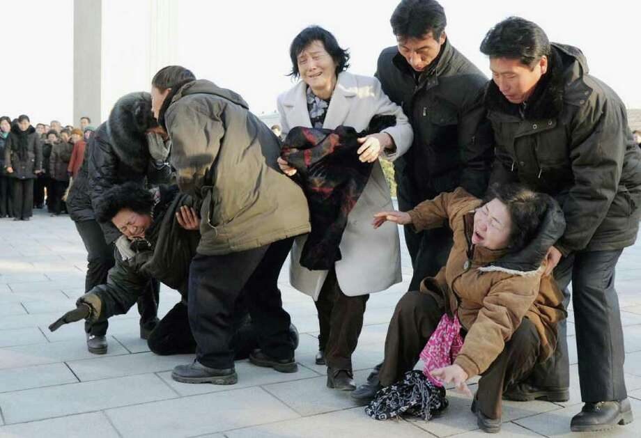 Women collapse in tears as North Koreans gather after learning death of their leader Kim Jong Il on Monday, Dec. 19, 2011 in Pyongyang, North Korea. Kim died on Saturday, Dec. 17, North Korean state media announced Monday. (AP Photo/Kyodo News) JAPAN OUT, MANDATORY CREDIT, NO LICENSING IN CHINA, FRANCE, HONG KONG, JAPAN AND SOUTH KOREA Photo: AP