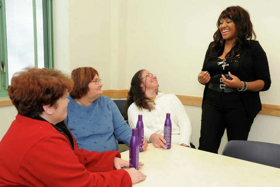 Tanisha Akinloye speaks to Spooner House residents, from left, Cari LeClair, Susan Romano and Doris Montalvo, during a training seminar at the shelter in Shelton, Conn. Dec. 19th, 2012. Akinloye runs Beauties of Charities, a non-profit providing beauty and wellness services to people living in local shelters. Photo: Ned Gerard / Connecticut Post