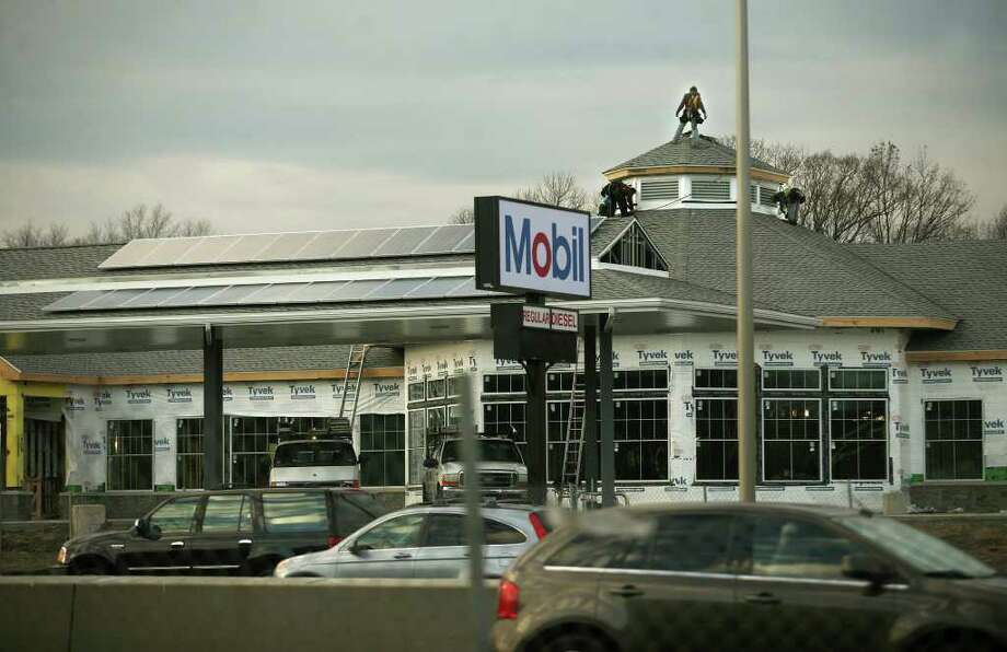 Construction workers finish the roof of the new service plaza on southbound I-95 in Milford on Monday, December 19, 2011. Solar panels have been placed on the southern exposure roofs. Photo: Brian A. Pounds / Connecticut Post