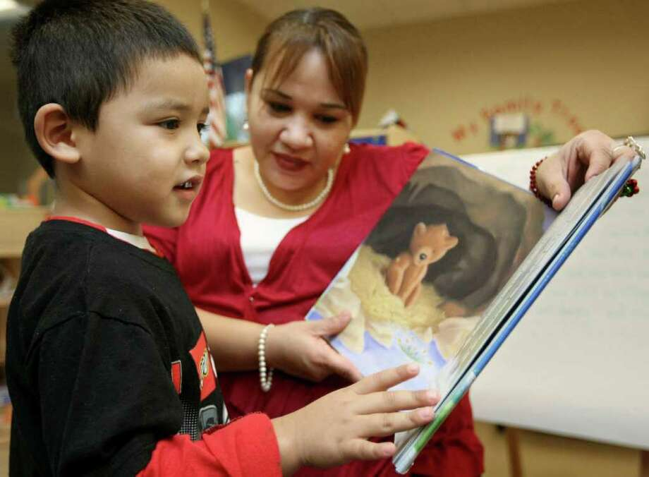 Four-year-old Richard Torres, left, reads a book with his mother, Nancy Garcia, Monday, Dec. 12, 2011, at the Daughters of Charity DePaul Children's Center in San Antonio. Photo: Darren Abate
