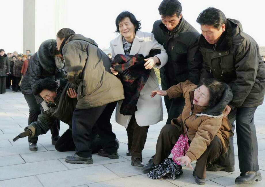 Women collapse in tears as North Koreans gather after learning death of their leader Kim Jong Il on Monday, Dec. 19, 2011 in Pyongyang, North Korea. Kim died on Saturday, Dec. 17, North Korean state media announced Monday. (AP Photo/Kyodo News) JAPAN OUT, MANDATORY CREDIT, NO LICENSING IN CHINA, FRANCE, HONG KONG, JAPAN AND SOUTH KOREA Photo: AP / Kyodo News