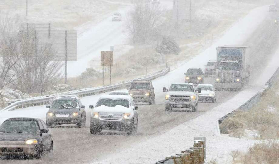 Inbound traffic on I-25 approaches Santa Fe, N.M. in a single file as snow accumulates on the road, Monday Dec. 19, 2011 as a winter storm hit the area. New Mexico state police say a winter storm is shutting highways and causing difficult driving across northern New Mexico. Los Alamos National Laboratory and a number of schools have closed as the storm moves across New Mexico and into the Texas and Oklahoma Panhandles and parts of Kansas and Colorado. Photo: CLYDE MUELLER, ASSOCIATED PRESS