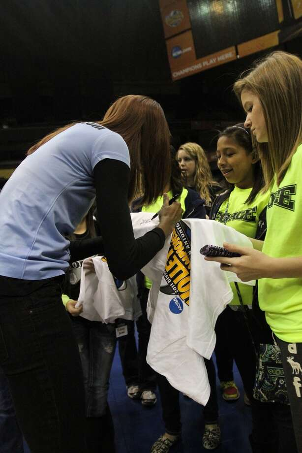 Members of the San Antonio Force volleyball club get shirts autographed by former Southwest volleyball star and U.S. Olympian Destinee Hooker during a VIP tour of the Alamodome Saturday. The NCAA Division I women's volleyball championships were held last weekend at the dome. Photo: Photo Courtesy/San Antonio Sports Foundation
